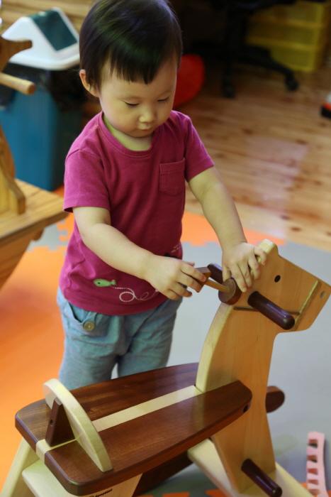 목마 손잡이부분을 만지며 놀고있는 아이