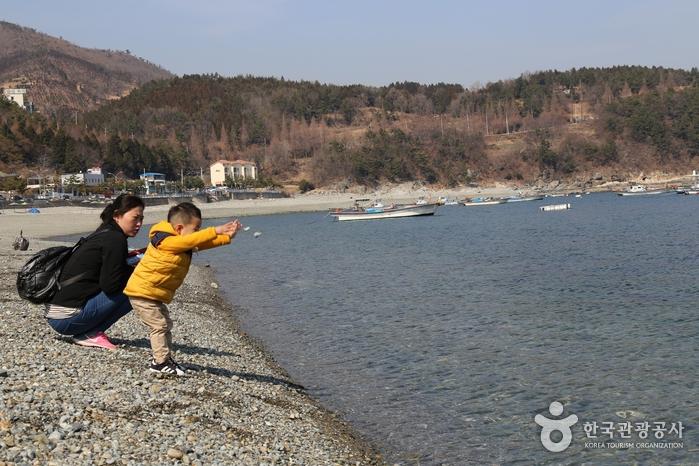 몽돌을 던지고 있는 검은모래해변의 아이