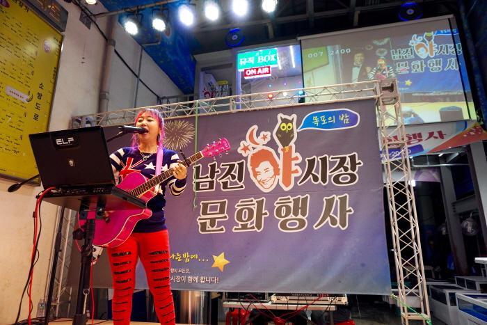 야시장 라이브 무대에서 통기타 가수의 공연이 펼쳐진다.