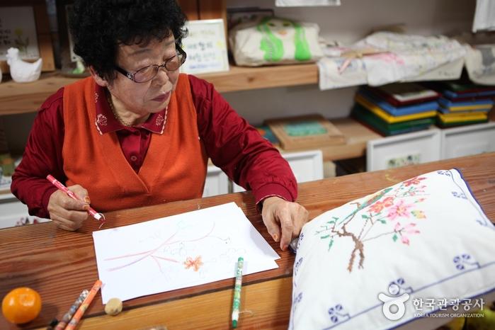 박정순 할머니는 쿠션에 새겨진 나무 그림을 따라 그려보기로 했다