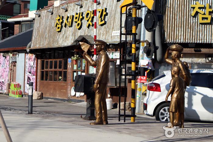 땡땡거리 입구에 역무원과 길을 건너려는 가족 모습을 나타내는 조각상
