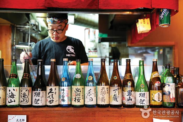 문타로 식당 일부 풍경(스탠드에 일본 술이 진열되어 있고 그 너머로 요리사가 요리에 집중하는 모습)