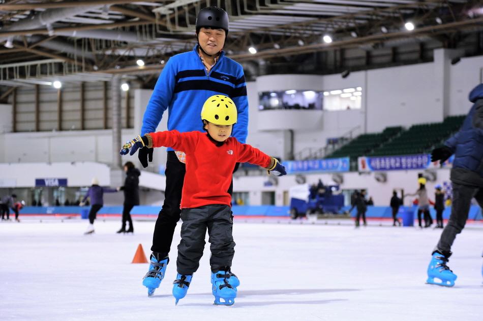 아빠에게 스케이팅을 배우는 어린이