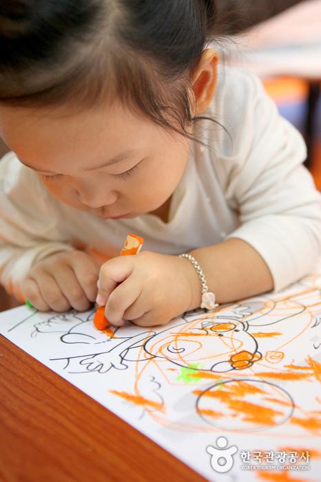 그린세이프놀이터에서 색칠하기에 빠진 어린이.
