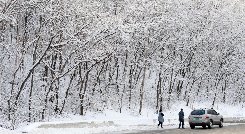 눈이 많이 내린 도로 위에 차를 정차해두고 내린 사람 두명.