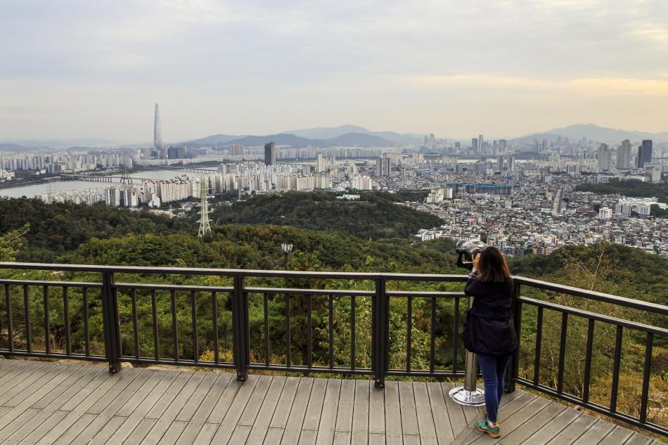 고배율 망원경으로 서울 시내 전경을 보는 관람객