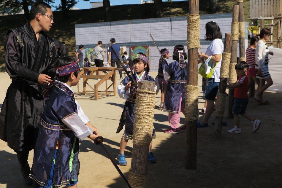 축제장에서 복장과 무기를 갖추고 체험하는 아이들