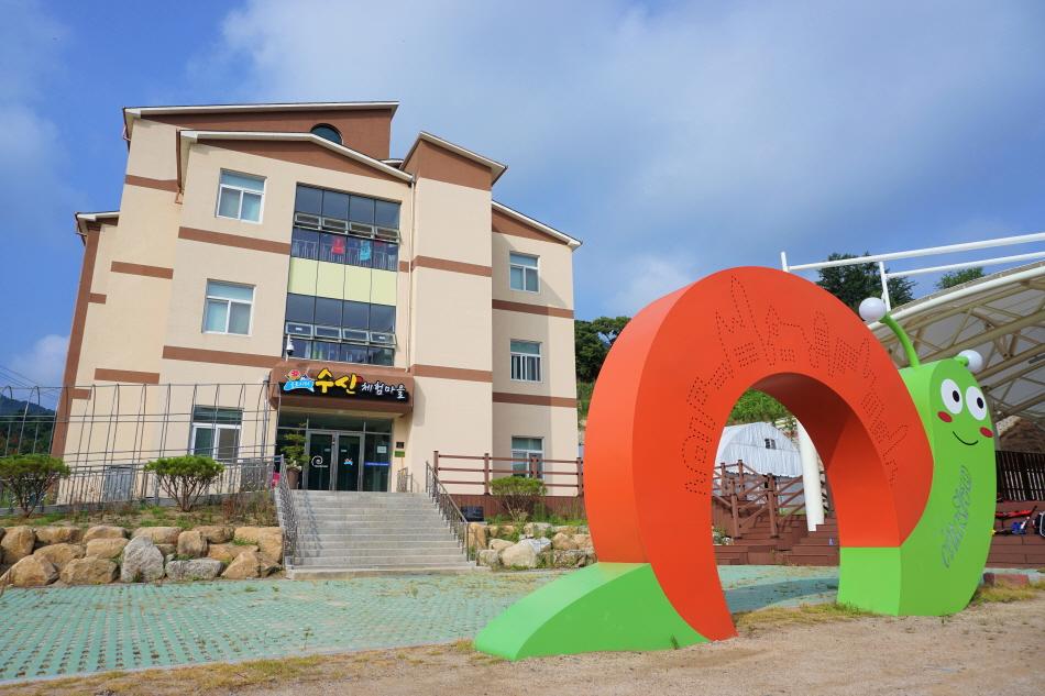 슬로시티수산을 상징하는 달팽이 모형과 폐교를 활용한 마을 숙소