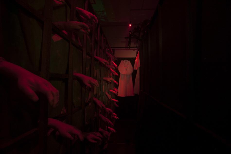 벽에 매달려 있는 수많은 손모형, 벽 끝에는 소복이 걸려있다