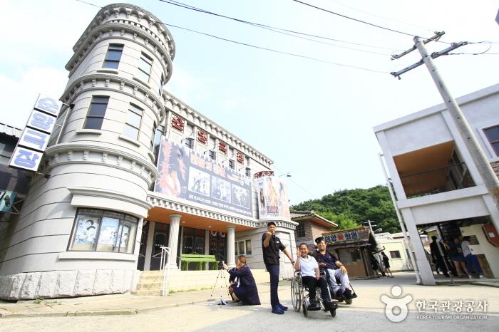 교복 포토 존 순양극장 전경-순양극장 앞에서 각기 휠체어를 탄 여성과 남성, 그리고 서있는 한 남성이 80년대 교복을 입고 사진을 찍기위해 포즈를 취하고 있다