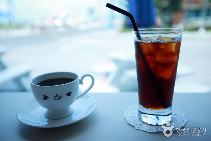 바다가 보이는 창가의 따뜻한 커피 한잔과 아이스 아메리카노 한잔