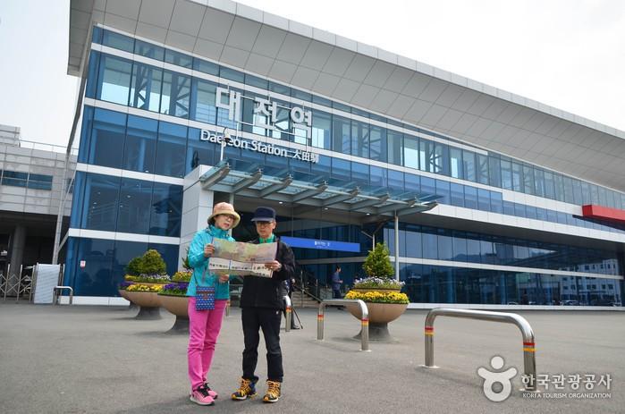대전역을 배경으로 지도를 펼쳐보고 있는 두사람
