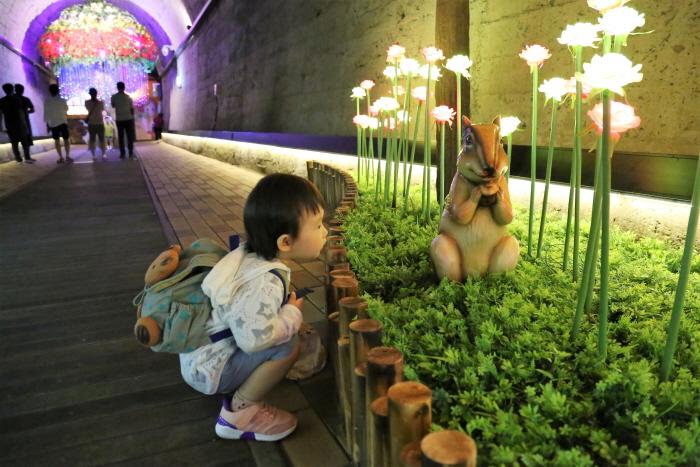어두운 동굴 안에서 LED장미꽃 앞에 쪼그려 앉아있는 아이모습