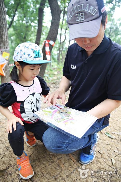 아빠와 딸이 나침반을두고 지도를 보고있다.