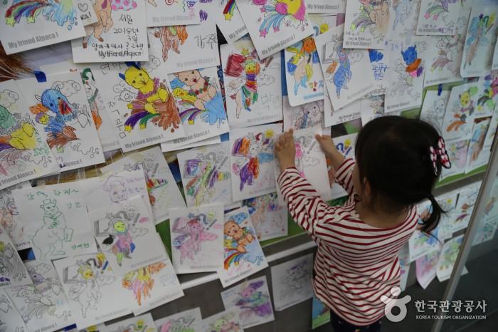 색칠한 알파카를 벽에 붙이는 아이