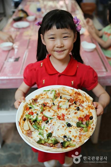 완성된 피자를 들고 있는 어린이