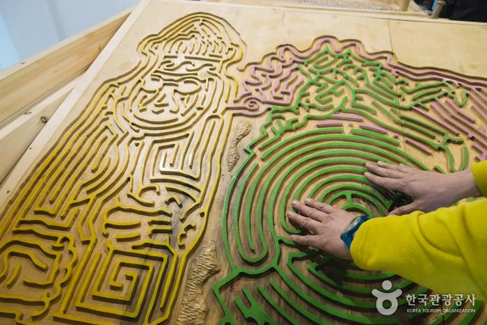 미로퍼즐의 복잡한 모양을 촉감으로 즐기는 여행객