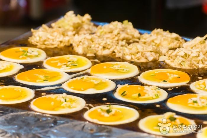 야시장 인기 야식 - 달걀과 반죽이 동그란 틀에 구워지고 있는 모습