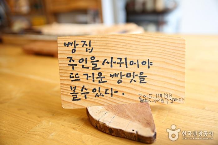 빵집 주인을 사귀어야 뜨거운 빵맛을 볼수있다. 라고 적힌 나무판