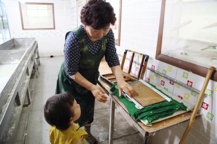 아이가 도움으르 받아 한지를 만들어보고 있다.