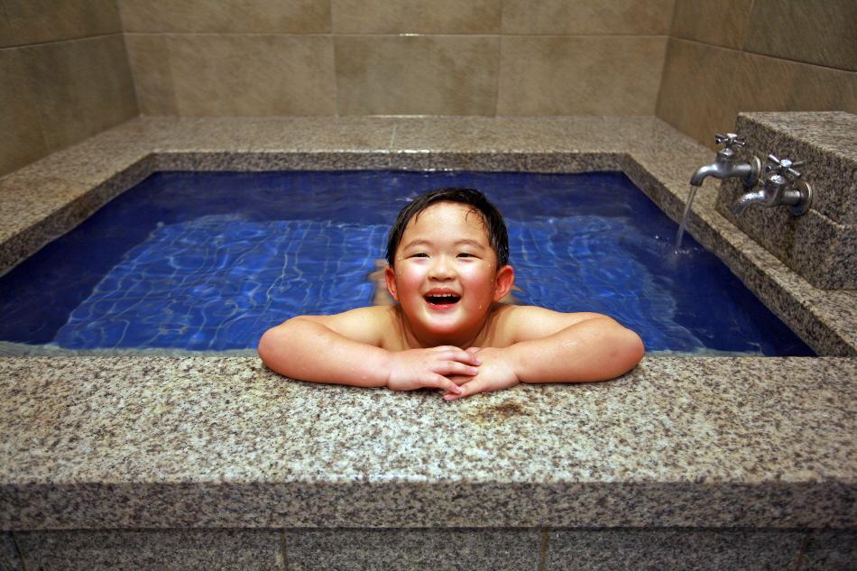 할매탕 가족탕에서 온천욕을 즐기는 어린이