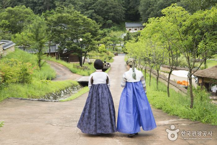 한복을 걷고 길을 걷는 사람 두명의 뒷모습