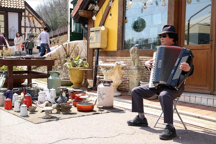 벼룩시장 앞에서 아코디언을 연주하는 거리의 악사