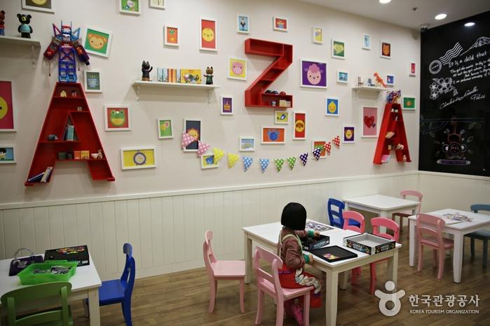 키즈월드의 미술을 체험하는 공간, 벽에 아기자기한 소품들과 액자들이 걸려져 있다.