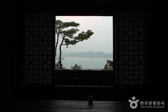 한옥 실내에서 바라본 창 밖 풍경, 멀리 산과 바다가 보인다