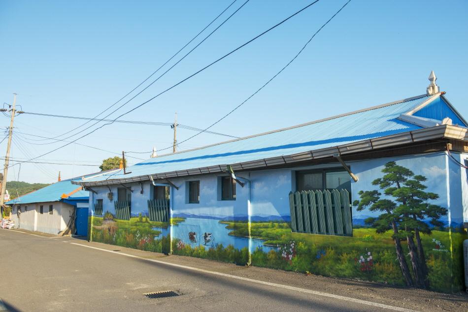초록의 나무와 푸른 강줄기가 그려져 있는 집 외벽