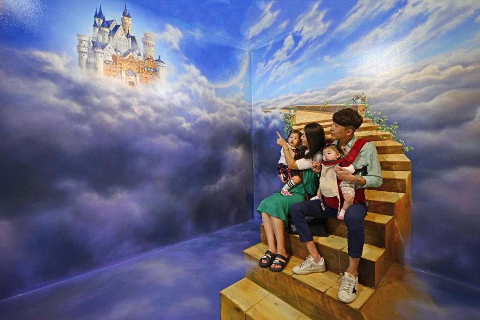 트릭아트스토리에서 즐거운 시간을 보내는 가족
