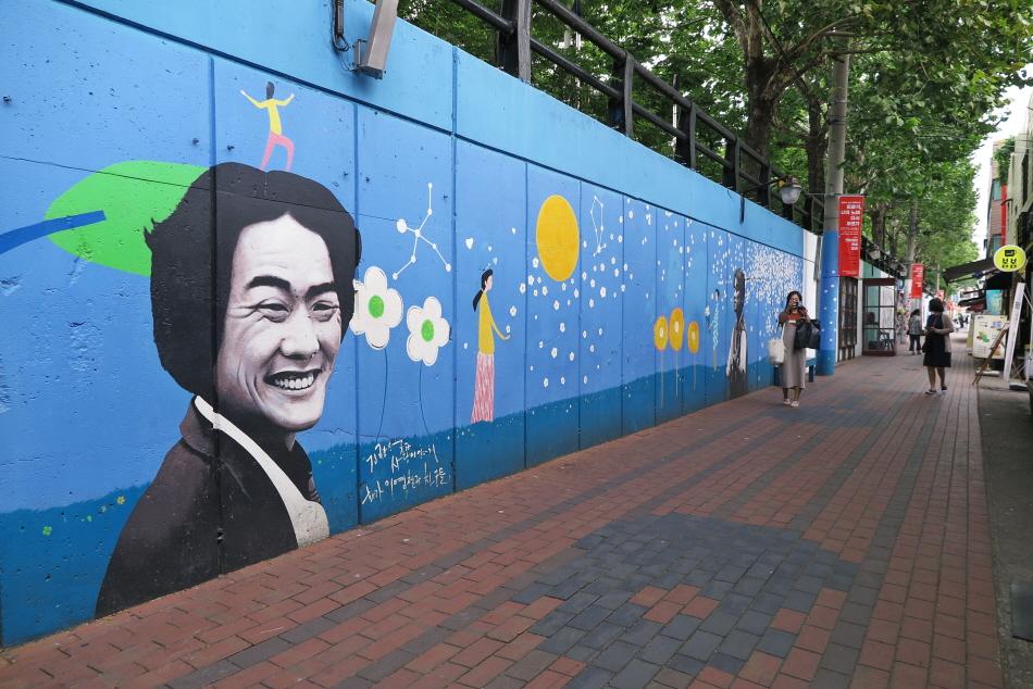 웃고 있는 김광석 얼굴 주변으로 꽃 등이 그려진 벽화길