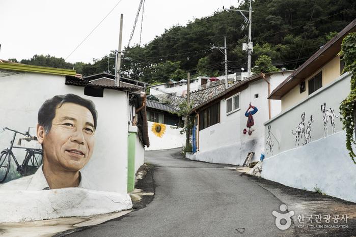 마을 주민의 얼굴이 사람 키보다 크게 그려져 있는 벽화, 스냅사진과 같은 벽화.