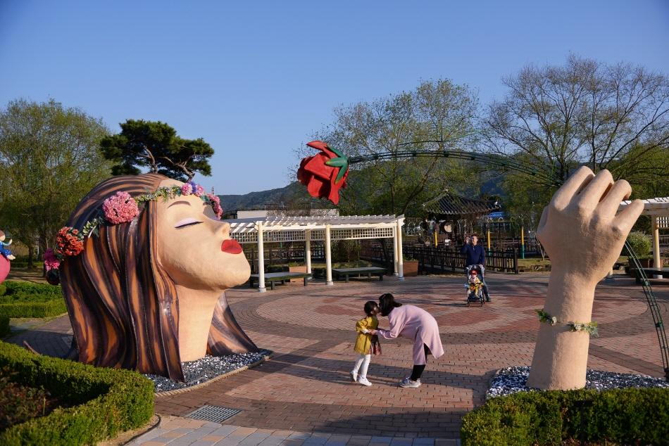 장미꽃을 든 여인 조형물 앞에서 기념사진을 찍는 가족