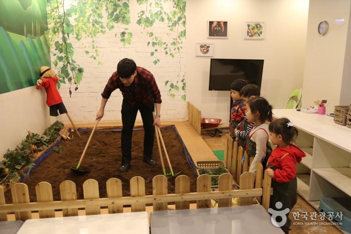 농부체험 - 실내안 작은 텃밭에서 남자가 밭을 갈고 있고 아이들은 그 모습을 바라보고 있다.
