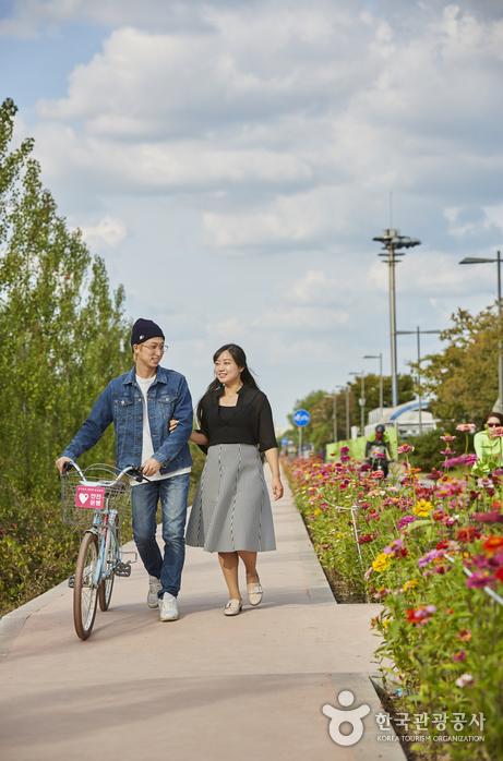 청명한 하늘, 길 옆으로 핀 꽃, 자전거를 끌고 걷고있는 커플