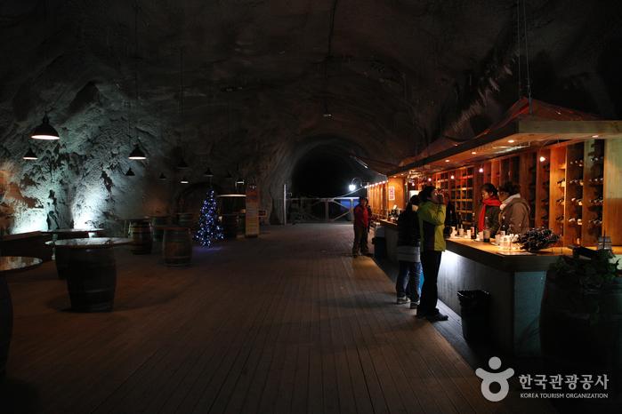머루와인동굴 안 풍경. 어두운 동굴안을 은은한 조명으로 빛을 밝히고,오른쪽에서 사람들이 머루와인을 시음하고 있다.