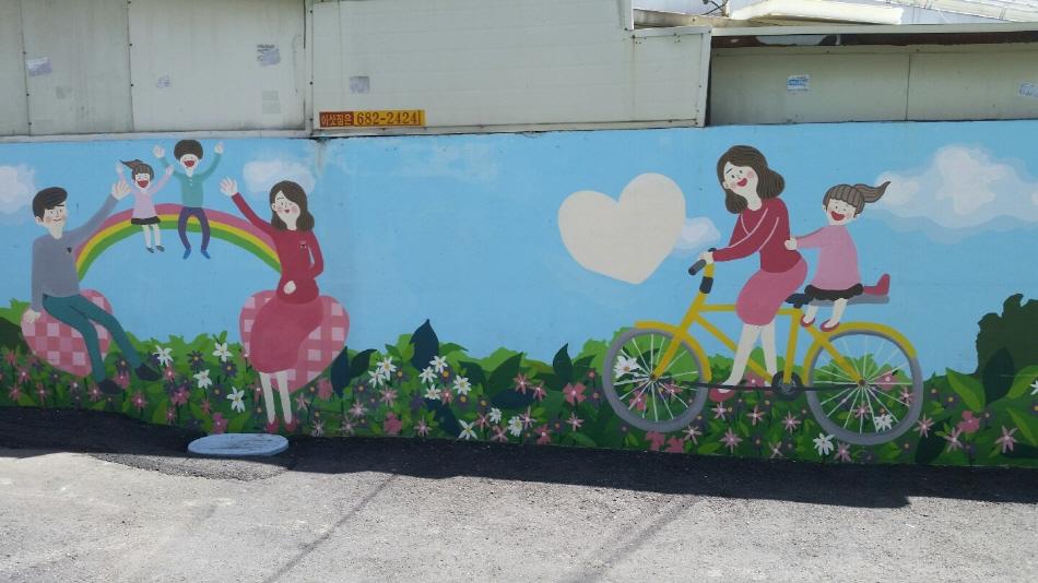 무지개 위에서 뛰어노는 아이들, 엄마와 자전거 타는 아이등을 그려넣은 벽화