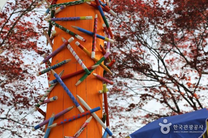 동그란 기둥에 색연필들이 매달려 있다.