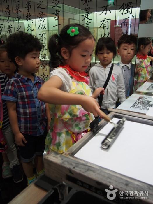 목판인쇄체험 - 롤러로 목판을 밀고 있는 아이