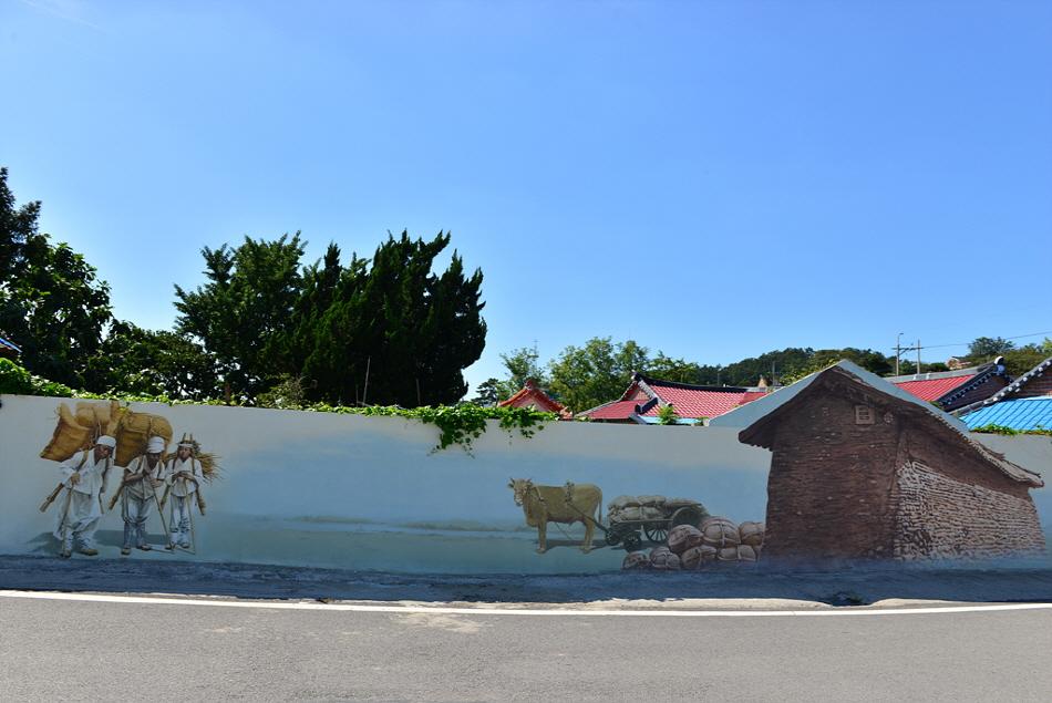 짐을 끄는 소와, 지게를 진 세 명의 남자가 그려져 있는 벽화