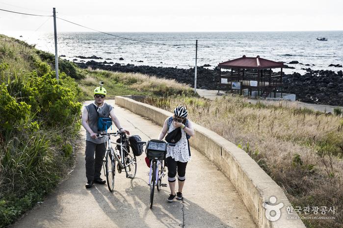 오르막길에서 자전거를 끌고 올라오고 있다.