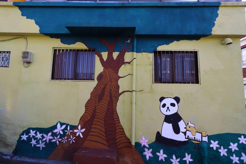 나무 앞에서 주사를 맞고 있는 팬더곰 벽화