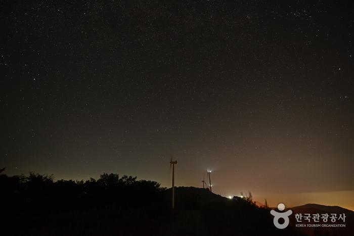 풍력발전기 뒤로 보이는 무수히 많은 별