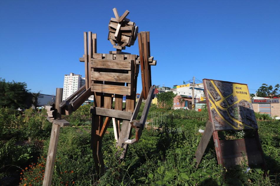 풀밭에 세워져 있는 나무판자로 만든 로봇 조형물