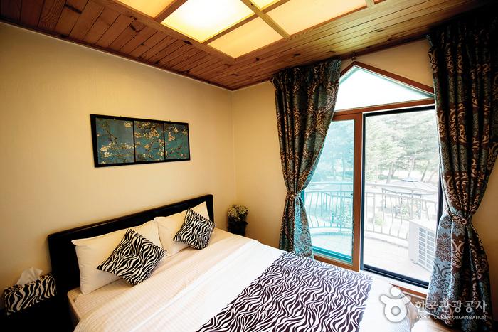 펜션 내부 침실. 얼룩말 무늬의 쿠션과 이불이 있다.