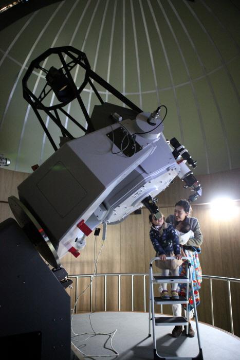보현산천문과학관 주관측실에서 아이가 망원경을 통해 하늘의 별을 보고 있다