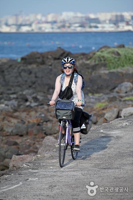 여자가 바다를 끼고 자전거를 타고있다.