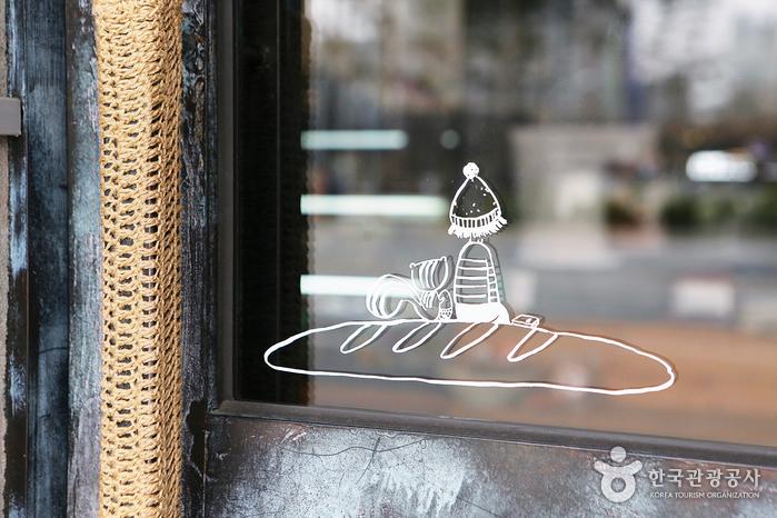 쿠아레 비 창문에 빵위에 앉아있는 사람과 다람쥐 그림이 그려져있다.
