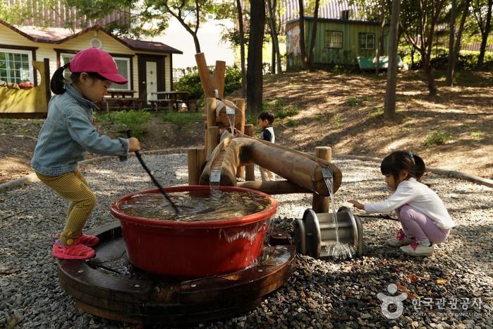 작은 물레방아에서 나오는 물로 노는 어린이들